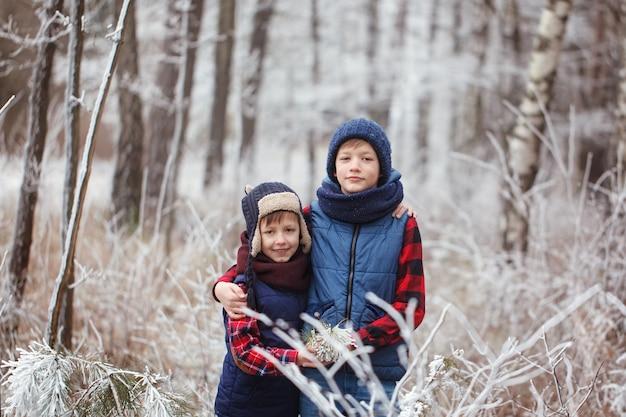 Dois irmãos em walr na floresta de inverno. melhores amigos jogando juntos.