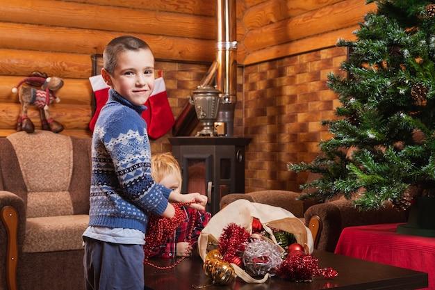 Dois irmãos estão ajudando a decorar a árvore de natal com miçangas vermelhas