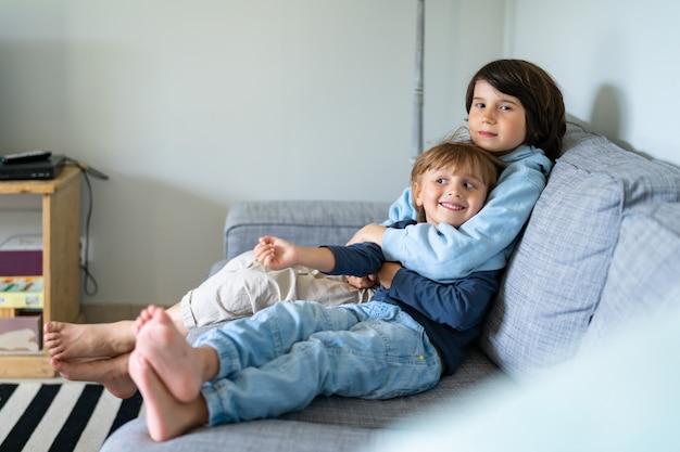 Dois irmãos estão sentados em um sofá em casa. o menino mais velho abraça o mais novo. boas relações entre irmãos.