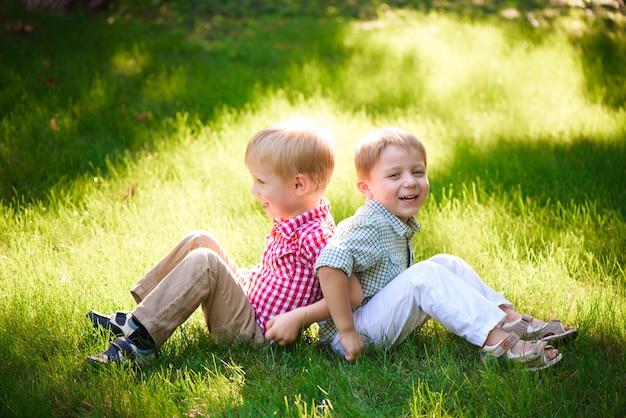 Dois irmãos estão sentados na clareira ensolarada no parque