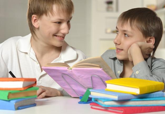 Dois irmãos fazendo lição de casa em casa à mesa