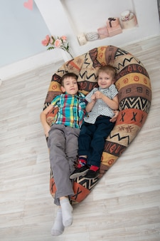 Dois irmãos felizes e amigáveis brincam e fazem cócegas um no outro, rindo, mentindo em uma tragada nacional. infância feliz emoções positivas e energia