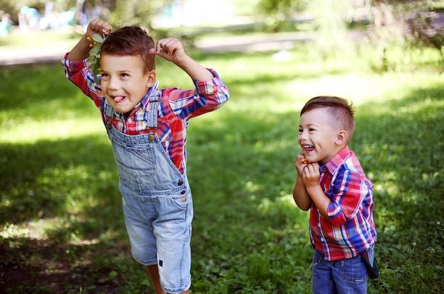 Dois irmãos felizes que têm o divertimento junto no parque do verão. meninos