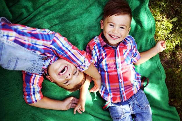 Dois irmãos felizes que têm o divertimento junto no parque.