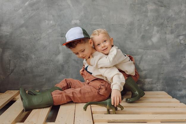 Dois irmãos felizes se abraçando sentados em paletes no conceito de fundo cinza de pequenos trabalhadores