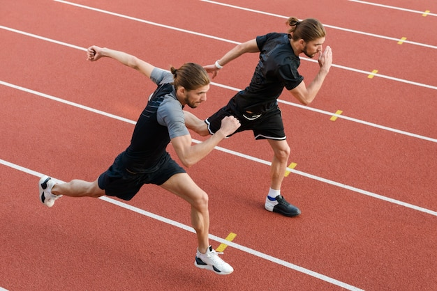 Dois irmãos gêmeos de desportistas correndo ao ar livre do estádio.