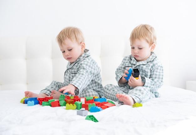 Dois irmãos gêmeos de meninos engraçados na cama branca de pijama jogando no construtor.