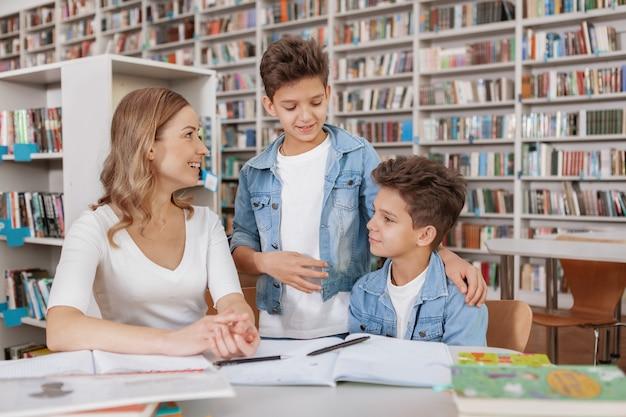 Dois irmãos gêmeos e sua mãe gostando de estudar juntos na biblioteca.