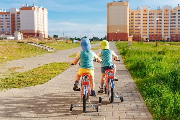 Dois irmãos gêmeos montando bicicletas juntos