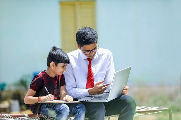 Dois irmãos indianos usando laptop, conceito de educação online