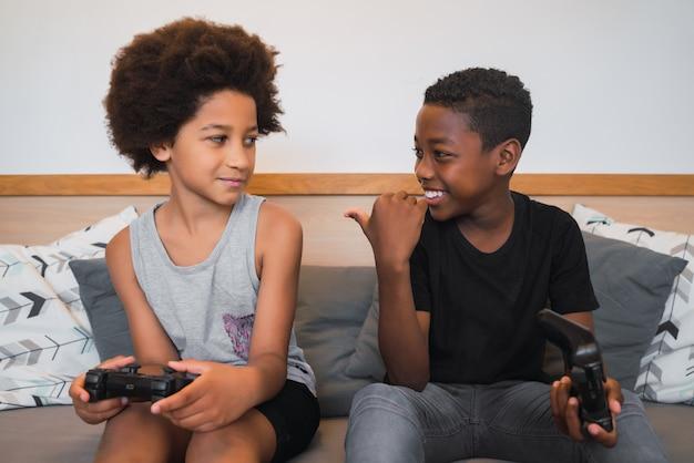 Dois irmãos jogando videogame em casa.