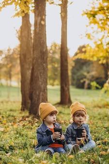Dois irmãos mais novos sentados na grama bebendo chá