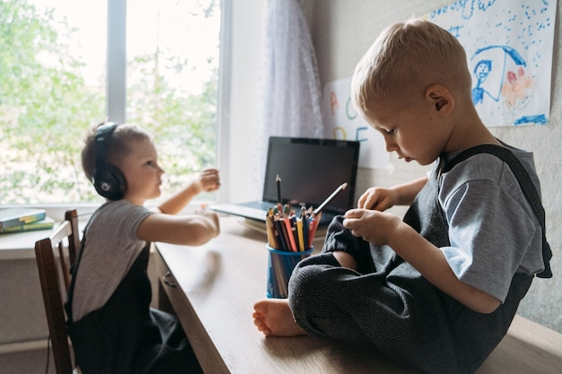 Dois irmãos meninos de escola usando fones de ouvido sentados perto de um laptop em casa, voltando para a escola