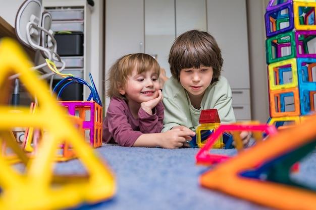 Dois irmãos passam um tempo juntos em casa com um brinquedo magnético