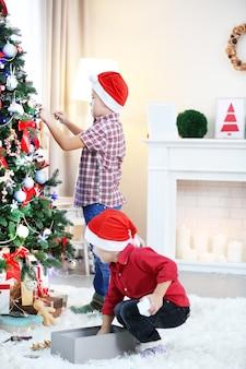 Dois irmãos pequenos bonitos decorando a árvore de natal
