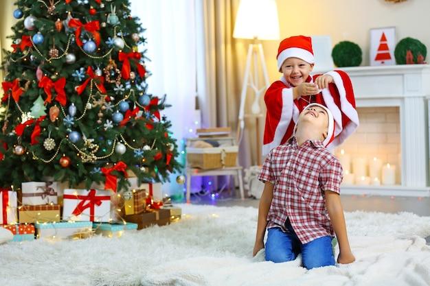 Dois irmãos pequenos bonitos no fundo da decoração de natal