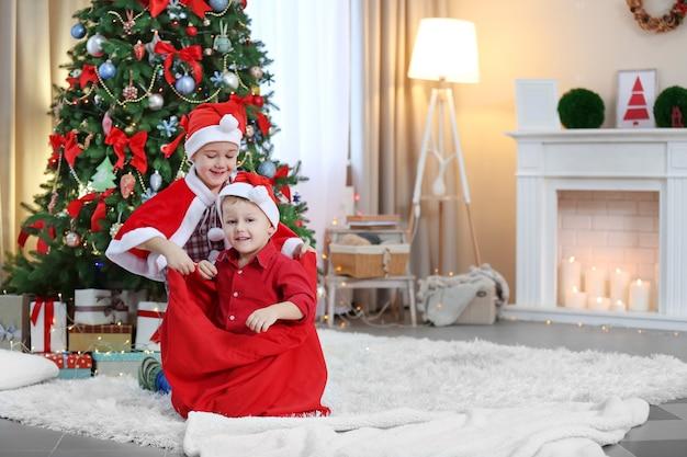 Dois irmãos pequenos brincando com a bolsa do papai noel no fundo da decoração de natal