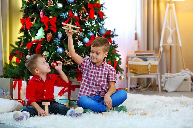 Dois irmãos pequenos brincando com um avião de madeira na árvore de natal