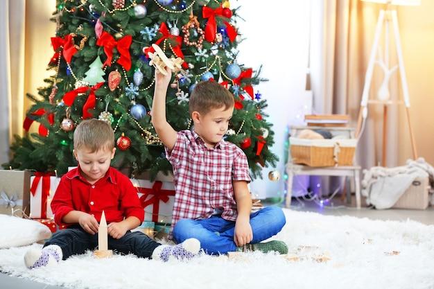 Dois irmãos pequenos brincando com um avião de madeira no fundo da árvore de natal