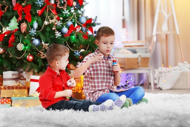 Dois irmãos pequenos e fofos soprando bolhas de sabão no fundo da árvore de natal