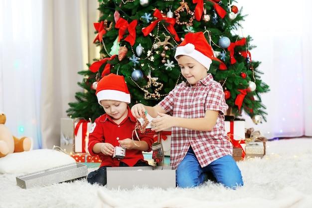 Dois irmãos pequenos fofos abrindo presentes no fundo da decoração de natal
