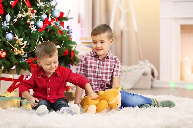Dois irmãos pequenos fofos com ursinho de pelúcia na árvore de natal