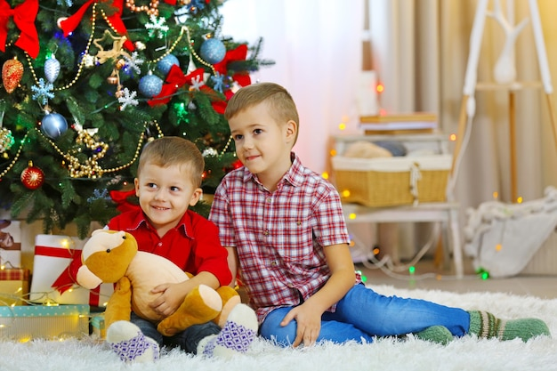 Dois irmãos pequenos fofos com ursinho de pelúcia no fundo da árvore de natal