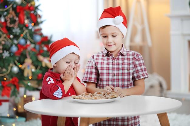 Dois irmãos pequenos fofos comendo biscoitos na decoração de natal