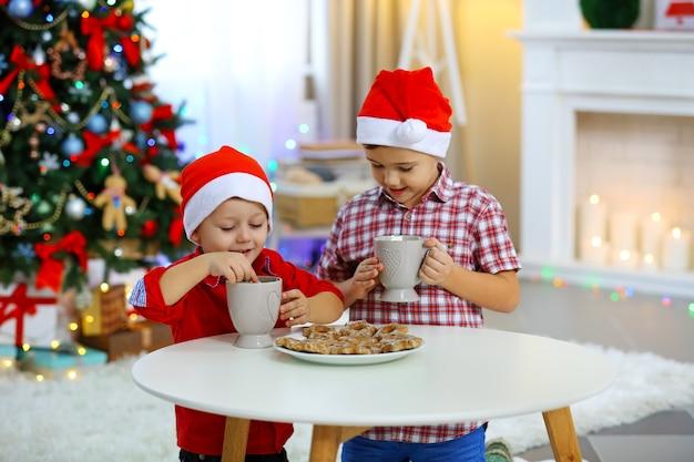 Dois irmãos pequenos fofos comendo biscoitos no fundo da decoração de natal