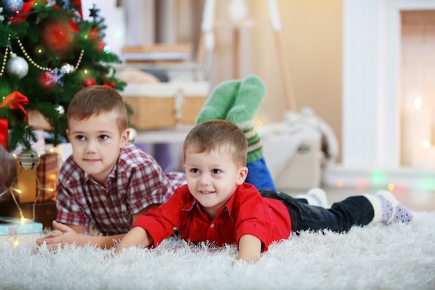 Dois irmãos pequenos fofos deitados no tapete no fundo da árvore de natal