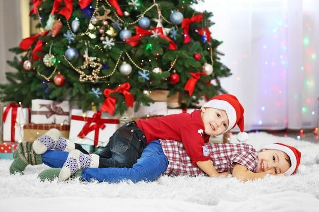 Dois irmãos pequenos fofos deitados no tapete no fundo da decoração de natal
