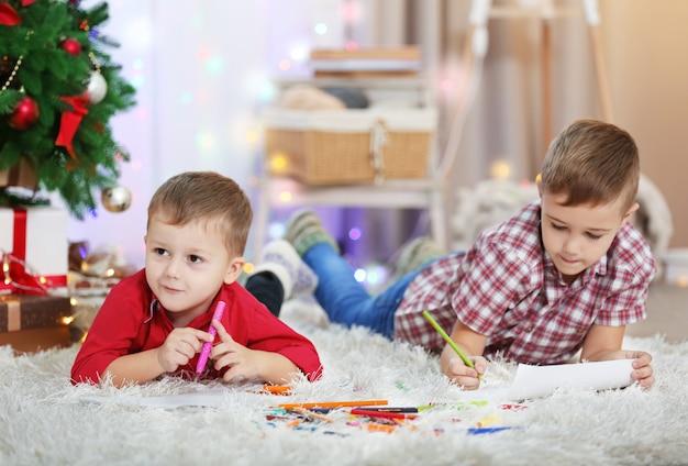 Dois irmãos pequenos fofos desenhando no fundo da árvore de natal