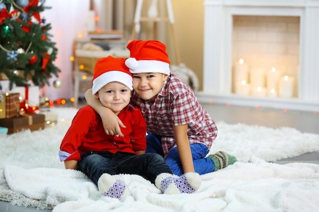 Dois irmãos pequenos se abraçando no fundo da árvore de natal