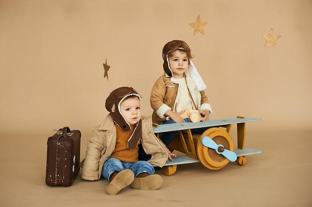 Dois irmãos são jogados com um avião de brinquedo e uma mala em um fundo bege. sonhos e viagens