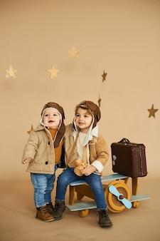 Dois irmãos são jogados com um avião de brinquedo e uma mala em um fundo bege