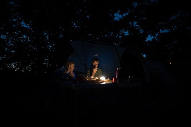 Dois irmãos sentados perto de sua tenda em um acampamento jantando sob uma luz fraca.