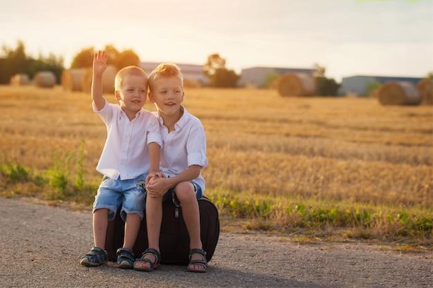 Dois irmãos sentam em uma mala na estrada no verão ao pôr do sol