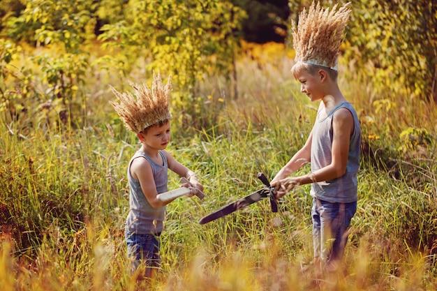 Dois irmãos têm uma coroa de grama seca na cabeça e espadas nas mãos.
