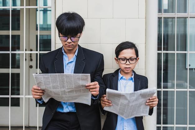 Dois irmãos usando óculos com camisa azul e paletó preto lendo jornal