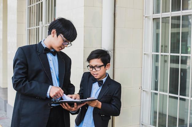 Dois irmãos usando óculos com fita preta e paletó preto vintage em pé, segurando e lendo um caderno