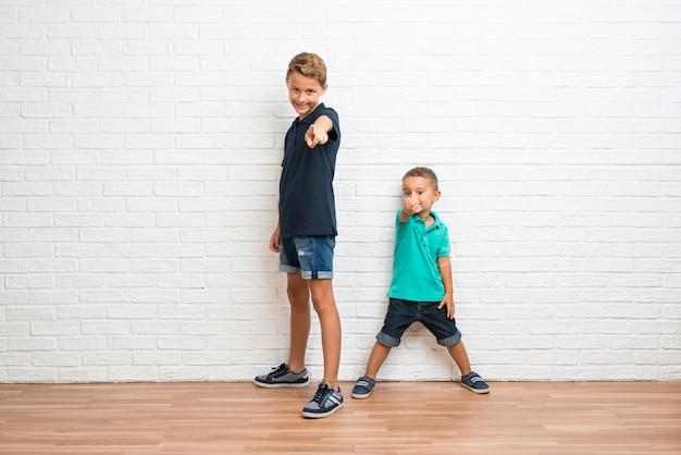 Dois irmãozinhos apontam o dedo para você com uma expressão confiante