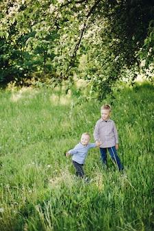 Dois irmãozinhos felizes vestindo jeans e camisas andando no parque