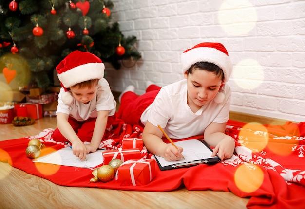 Dois irmãozinhos fofos escrevendo uma carta para o papai noel no ano novo de natal