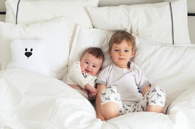 Dois irmãozinhos lindos e sorridentes na cama, manhã engraçada