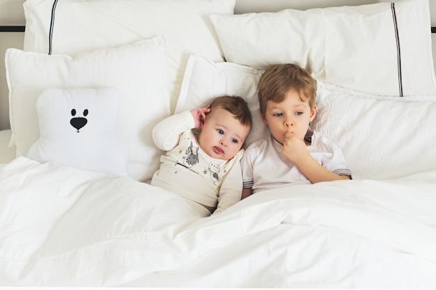 Dois irmãozinhos muito atenciosos na cama