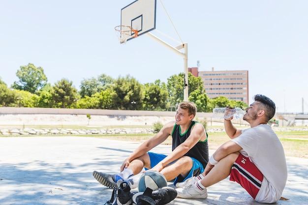 Dois, jogador basquetebol, relaxante, em, ao ar livre, corte