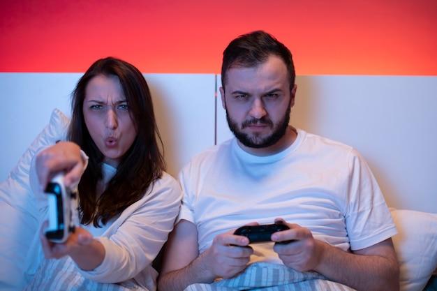 Dois jogadores apaixonados jogando videogame na cama com joysticks apaixonados e emocionais