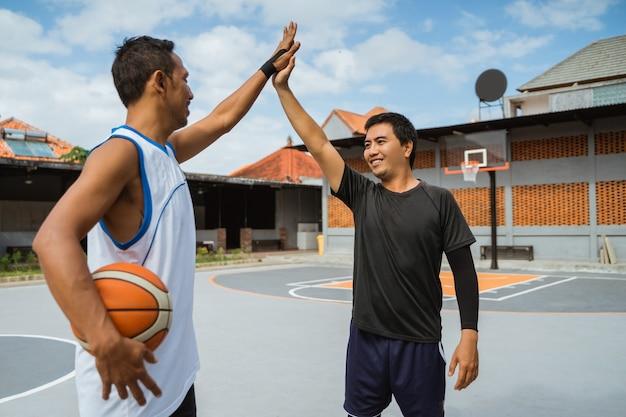 Dois jogadores de basquete do sexo masculino com high fives no intervalo jogando basquete