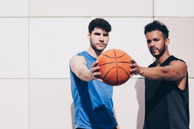 Dois jogadores de basquete na frente de uma parede