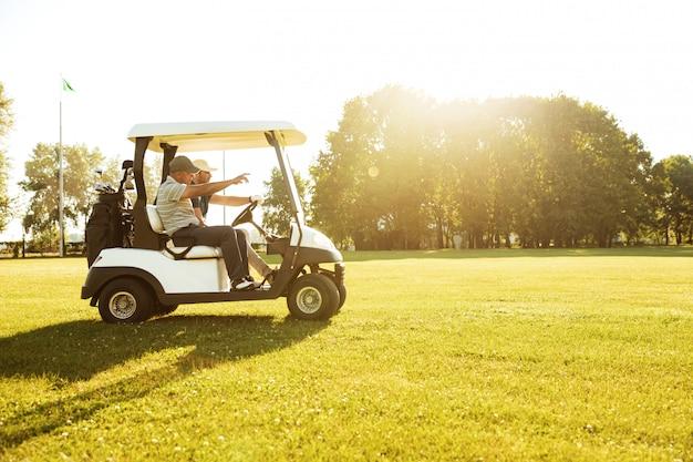 Dois jogadores de golfe masculinos dirigindo em um carrinho de golfe